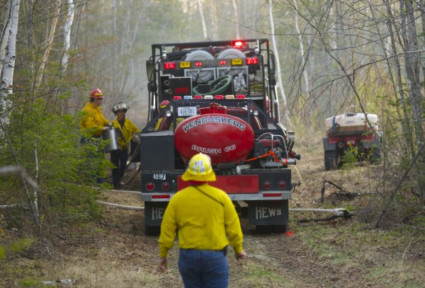 Fire crews fight a brush fire on a dirt road near the 2700 block of the Hudson Road in Hudson Monday evening.