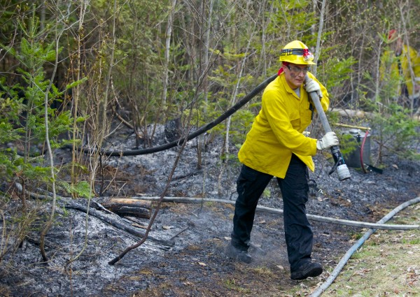 Fire crews fight a brush fire on a dirt road near in Hudson Monday evening.