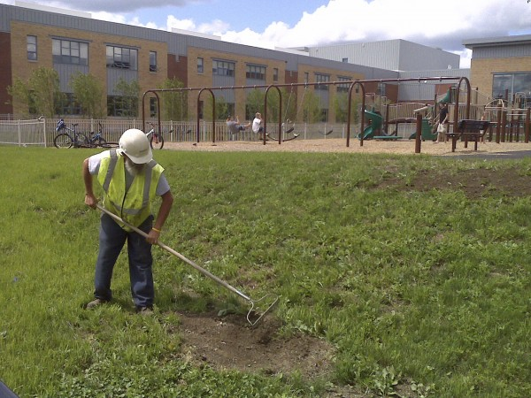 A worker rakes the grass in front of the Brewer Community School in August 2011.