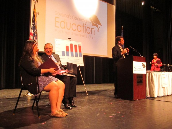Gov. Paul LePage (center) shares a laugh with Cony High School senior Michelle Zhang at the beginning of LePage's &quotPutting Students First&quot education summit in Augusta on Friday, March 22, 2013. Speaking at the podium is Education Commissioner Stephen Bowen.