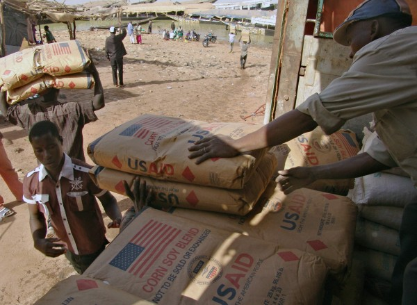 Men transport humanitarian food aid onto small flat bottom boats at Mopti in this February 4, 2013 file photo.