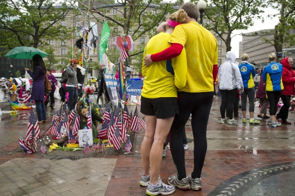 Katie Eastman (left) and Kiaren Shaughnessy visit the memorial on Copley Square after crossing the finish line and completing the final mile of the Boston Marathon course during One Run in Boston on Saturday. Eastman participated in the marathon on April 15 but was unable to finish when the course was shut down following the bombing attack.
