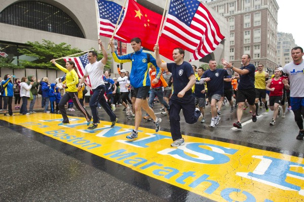 Runners holding American flags and a Chinese flag cross the finish line after completing the final mile of the Boston Marathon course during One Run in Boston on Saturday. The event was organized to give athletes and spectators an opportunity to complete the final mile of the Marathon that was cut short when two bombs exploded at the finish line on April 15.