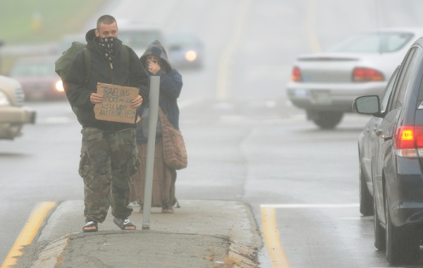 A man and his girlfriend panhandle along Hogan Road in Bangor on Wednesday, Sept. 5, 2012, in a rainstorm.