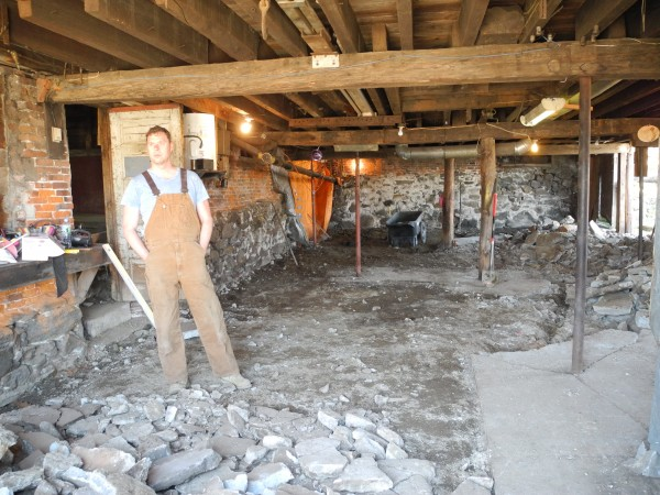 Greg Tinder stands in the basement he and his husband, Seth Thayer, have been digging out by hand in the large structure they recently purchased in downtown Belfast with the goal of renovating it.