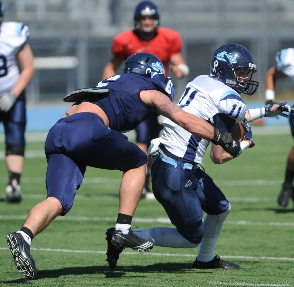 UMaine's Troy Eastman (left) brings teammate John Ebeling down after Ebeling caught the ball during the Maine Black Bear Football 2013 Jeff Cole Scrimmage on Saturday in Orono.