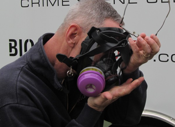 Rob Simmons of Gorham-based BioSpecialists LLC straps a respirator mask on Sunday morning before entering a vacant home where he and co-workers will train with a chemical agent that neutralizes the dangerous byproducts of meth labs.