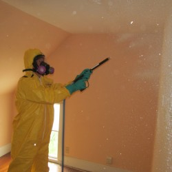 Rob Hunt of Gorham-based BioSpecialists LLC applies a neutralization agent to the walls of a vacant Standish home Sunday as part of a meth lab remediation training.