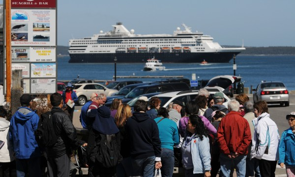 Passengers from the cruise ship Veendam wait in line to board a launch back to the cruise ship after spending the day in Bar Harbor Sunday.