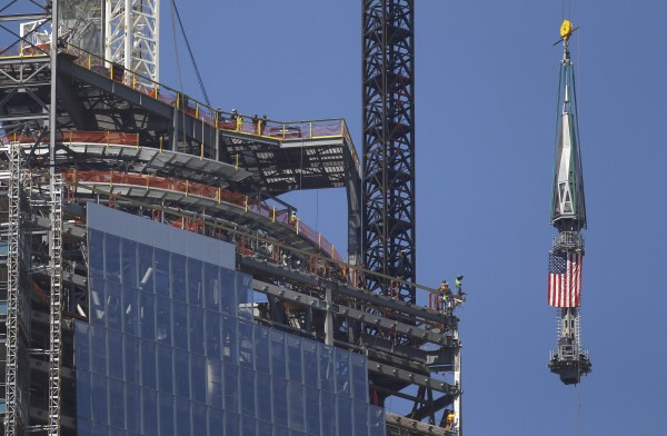The final section of the spire that will top off One World Trade Center is raised past iron workers to the top of the building in New York, May 2, 2013. The piece will be attached at a later date.