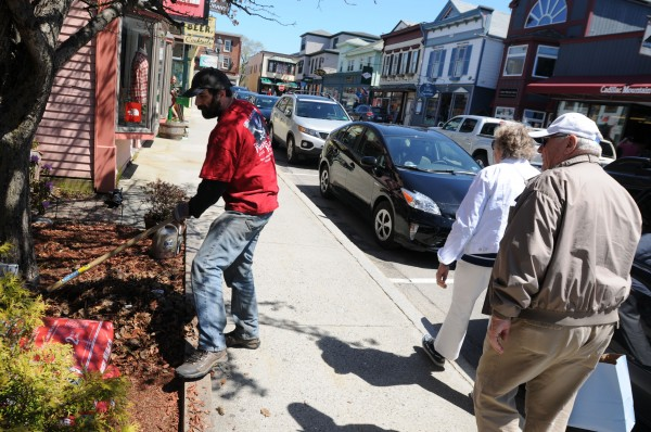 Matt Hockman, owner of the Opera House Internet Cafe and the Trailhead Cafe, rakes leaves as tourists walk the streets of Bar Harbor on Sunday.