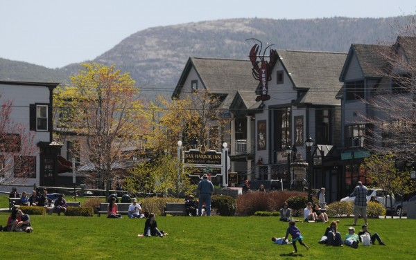 People lounge in Bar Harbor's Agamount Park on Sunday as the town's population swelled with the Sunday visit of the cruise ship Veendam.