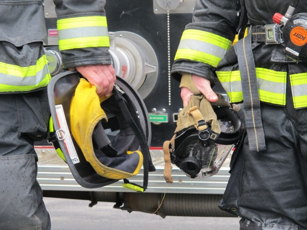 Ellsworth firefighters hold onto their helmets and masks after a sanitation demonstration on May 2, 2013.