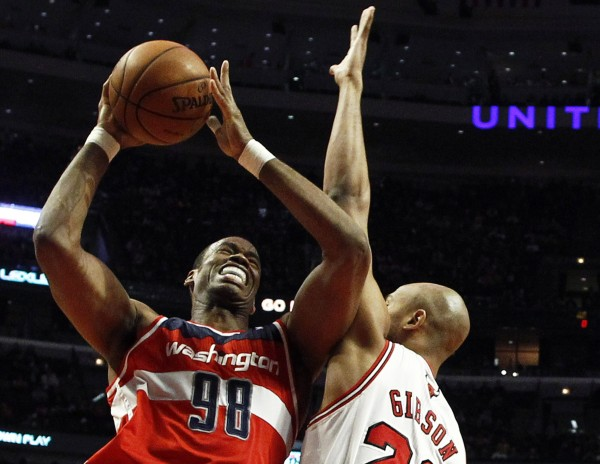 Washington Wizards' Jason Collins (L) goes to the basket against Chicago Bulls' Taj Gibson during the first half of their NBA basketball game in Chicago, Illinois, in this April 17, 2013 file photo.