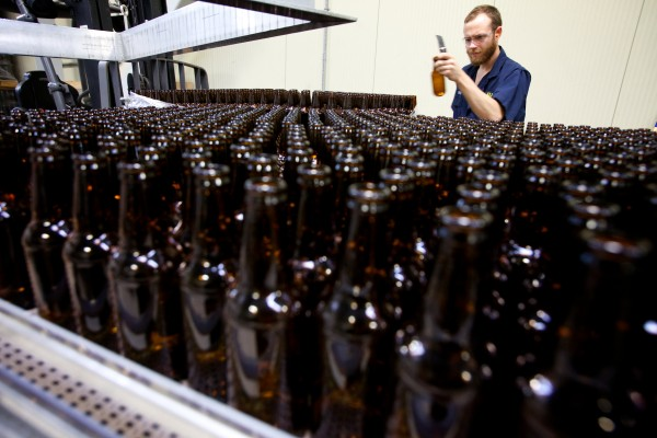 Brendan McKay checks a bottle before it gets filled at the Allagash Brewing Company in Portland on Wednesday. According to recent data, output by Maine breweries in 2012 increased by more than 20 percent for the third year in a row.