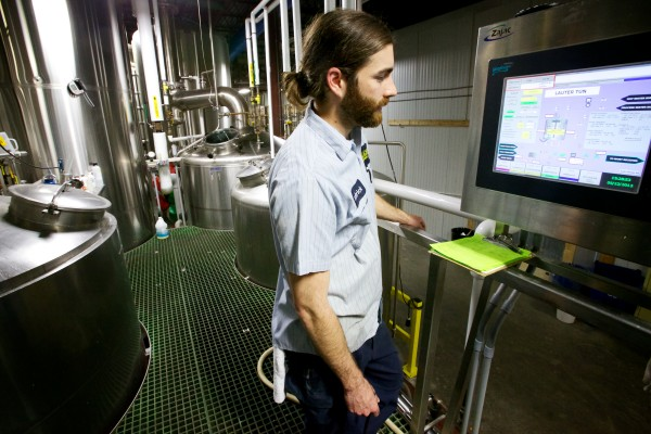 Patrick Saville monitors part of the brewing process at Allagash Brewing Company on Wednesday in Portland. Allagash is Maine's second-largest brewer.