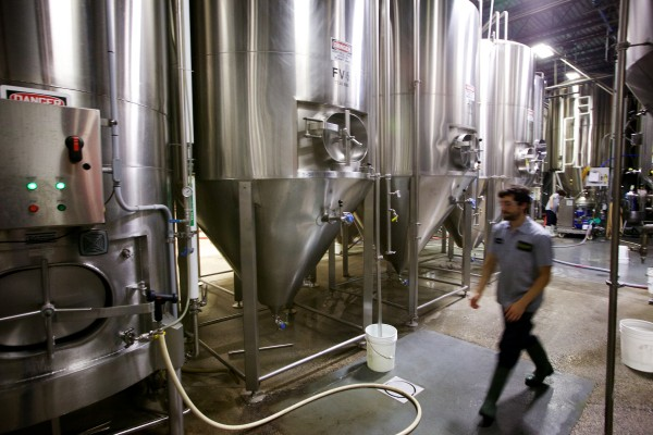 Workers produce beer at Allagsh Brewing Company in Portland Wednesday. The company is nearly finished with a project that will double its brewing and retail spaces, each by about 6,000 square feet, and it expects to add 15 positions this year for a total staff of about 70 employees.