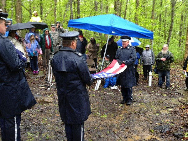 The Maine Air Guard's Maine State Honor Guard's members Saturday perform one of the three flag-folds, for presentation to members of the deceased crew members' families at the crash site.