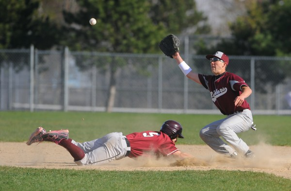 Ellsworth's Dustin Smelley (left) dives back to second base beating the pickoff throw to Washington Academy shortstop Tyler Varney during the game in Ellsworth Tuesday.