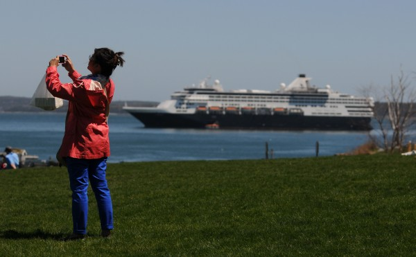 Cruise ship passenger Joy Roxas of California takes a picture with her cellphone as the cruise ship Veendam sits off Bar Harbor Sunday.