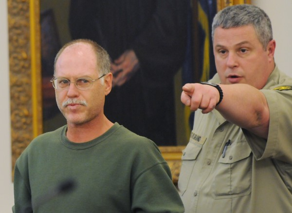 David Coon, left, of Bangor gets show to his seat at the Penobscot Judicail center in Bangor on Tuesday by a court security officer. Coon was making his initial appearance on a murder charge connection with the weekend death of Sherry Clifford.