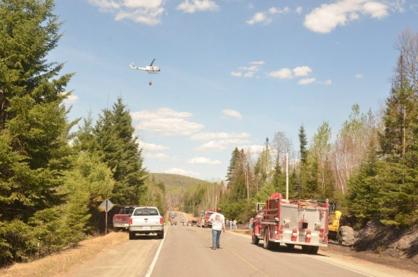 A helicopter carries water as fire crews battle a fire off Route 161 in St. Francis on Tuesday, May 7, 2013.