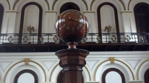 An 8-foot, four-sided walnut clock stands in the U.S. Custom House in Portland.
