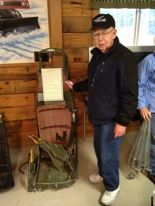 Survivor Capt. Jerry Adler stands next to the B-52 ejection seat in which he evacuated the bomber on Jan. 24, 1963. The seat is on display at the Moosehead Riders Snowmobile Club clubhouse in Greenville.