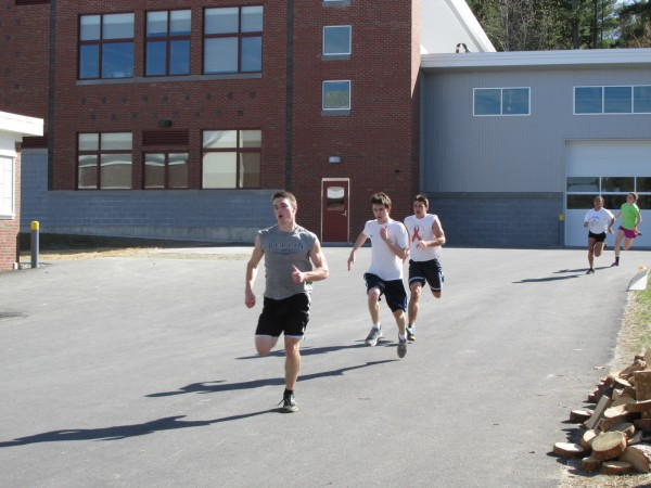 Members of the Old Town High School track and field team run downhill along the driveway behind the school as part of their practice regimen on Monday.