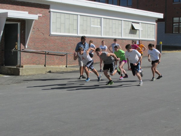 Members of the Old Town High School outdoor track and field team take part in a workout under the watchful eye of head coach Rod White on Monday afternoon. The Coyotes are sometimes practicing on the asphalt driveway behind the school while their track is being renovated.