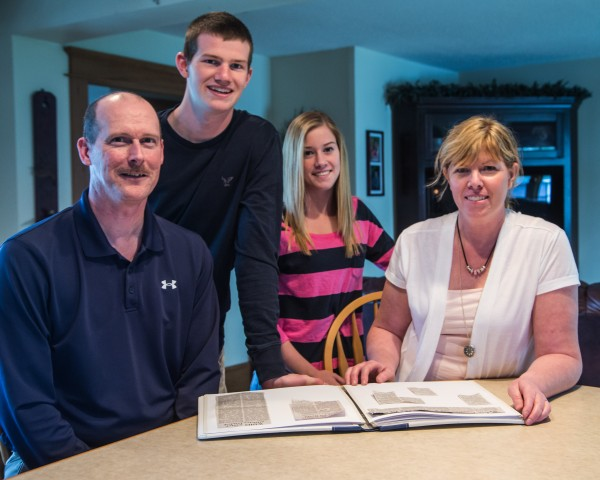 The Worcester family (from left), Larry, Mitch Mackenzie and Kim, peruses a scrapbook of newspaper clippings of stories dealing with their athletic careers in their home in Washburn recently.
