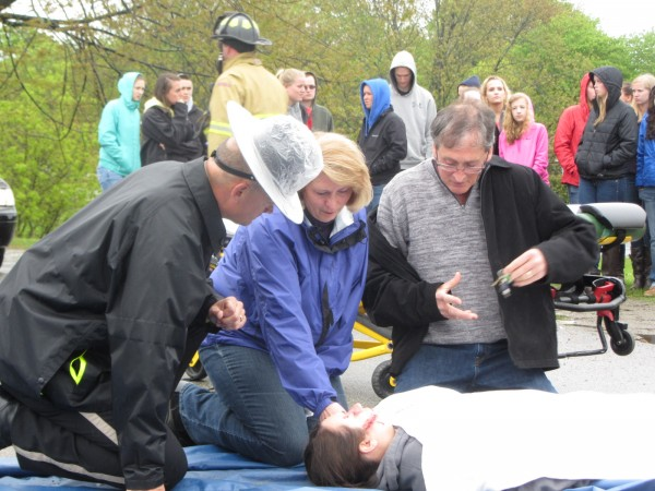 Dyann and Clyson Peters kneel over their daughter Shale Peters in the parking lot of Oceanside High School East in Rockland on Wednesday morning as part of the Every 15 Minutes program. The event that aims to make students aware of the dangers of drinking and driving. Knox County Sheriff's Office Chief Deputy Tim Carroll is kneeling with the parents.