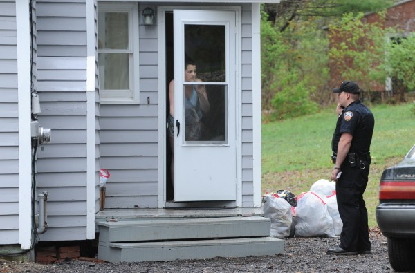Kara Sickles looks out the door of her 50 Mayo Road home as Hampden Police Officer Anthony Lorenz talks on his cellphone. Sickles was summoned on an assault charge after she allegedly shot two people with a pellet gun who were on her porch and refused to leave after demanding Sickles return a lost dog.