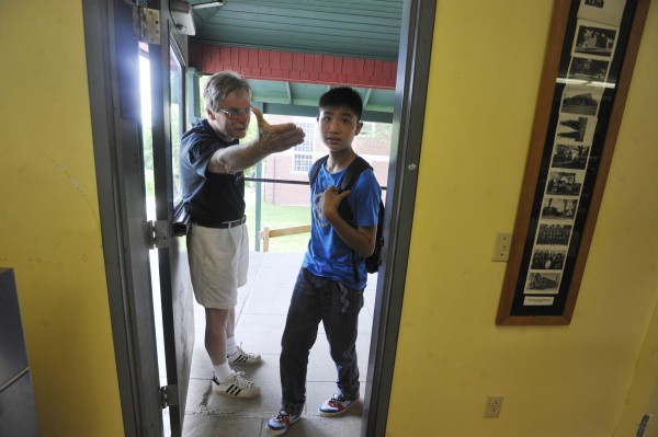 Lee Academy headmaster Bruce Lindberg, left, directs a student who referred to himself as &quotJames&quot  into the school cafeteria for brunch during his first day in Lee Friday, July 8. Fifty-two students from Guangzhou Foreign Language School are spending several weeks at Lee Academy to brush up on their English language skills.