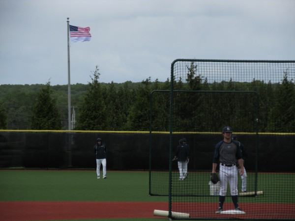 The University of Maine baseball team goes through its pregrame warmups as the wind whips across Bill Beck Field before Sunday's America East championship game at Kingston, R.I.