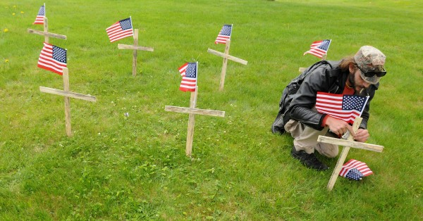 Eli Duncan sets up crosses at Mt. Hope Cemetery in Bangor Monday morning. Duncan and his mother Teresa Montague held a small demonstration to bring awareness to the high rate of suicide among veterans. Montague says that every day 22 veterans commit suicide in the US and sometimes it is due to the long wait in veterans' care.