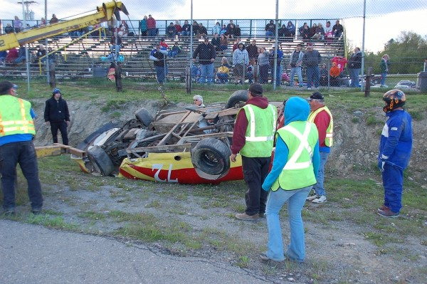 A crew works at Speedway 95 works to remove Mike Golding's car from the track after he flipped it during a race at the track Saturday night.