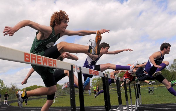 Competitors clear the first hurdles in the boy's 110 meter high hurdle semi-final race during the PVC Class B Track and Field Championship in Brewer Monday.