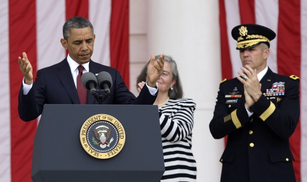 U.S. President Barack Obama directs people to be seated before his remarks as a part of Memorial Day observances at Arlington National Cemetery.