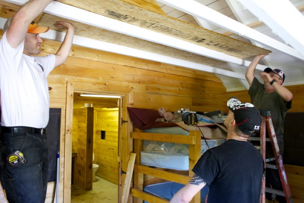 From left, Nolan Dubord, Brandon Sullivan and Buster Tyler work on one of the cottages at Camp Kennebec Tuesday afternoon in Belgrade.