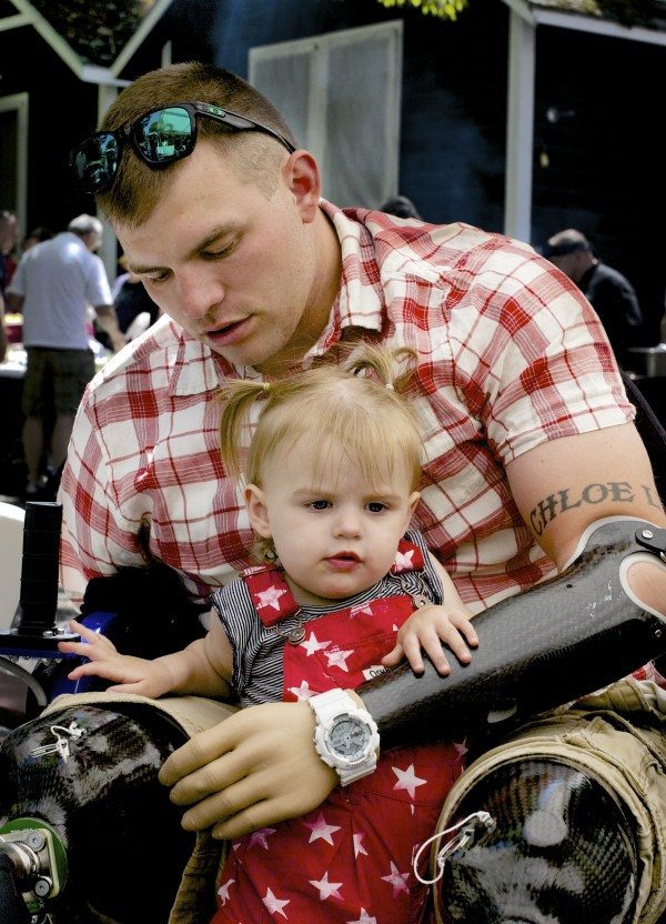 Travis Mills, an Afghanistan War Veteran and quadruple amputee, holds his daughter Chloe, 1, at Camp Kennebec in Begrade. Mills with the help of Bread of Life Ministries and Camp Kennebec are making the camp accessible for severely disabled veterans for a place to recover.