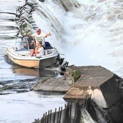 Paul Duclos of Lewiston talks with Auburn firefighters on the shore of the Androscoggin River just above the railroad trestle over the Great Falls on Thursday night after the motor on his boat died and it drifted downriver before getting hung up on the grates of the dam. His wife, Arlene, holds their dog, Reese, as they await rescue.