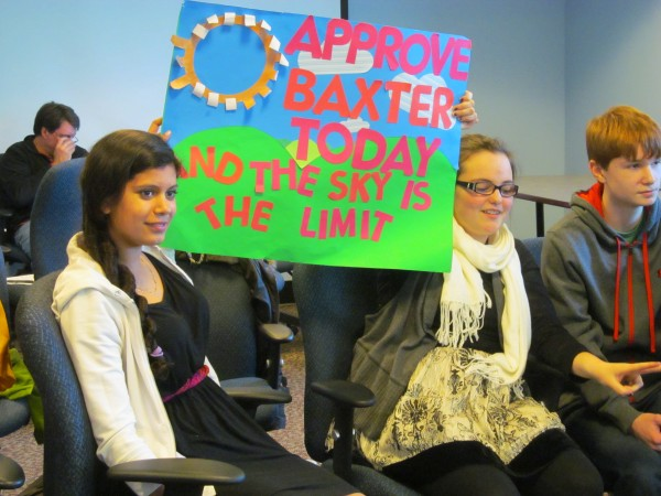 Nica Todd (left), 13, of Cumberland and Brianna Keliehor, 13, of Gorham, both of whom plan to attend Baxter Academy for Science and Technology when it opens in September, hold a sign in support of their school last month during a Maine Charter School Commission meeting in Augusta. The commission moved the project forward with a unanimous vote.