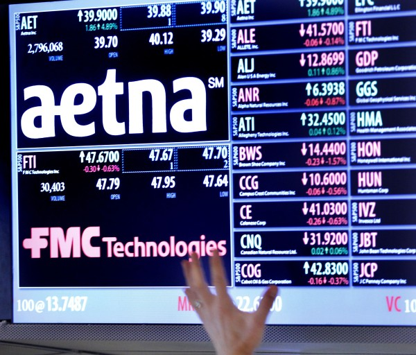 A trader points up at a display on the floor of the New York Stock Exchange in August 2012. Health insurer Aetna Inc. said Oct. 25, 2012, that it was able to hold down costs by directing more of its plans to U.S. medical providers that focus on efficient care, helping it beat quarterly profit expectations and raise its earning forecast for the year.