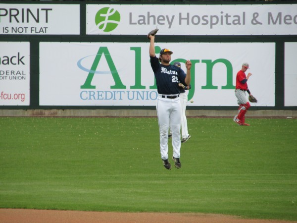 Scott Heath of Westbrook leaps to make a catch while warming up before the University of Maine's America East baseball tournament game Wednesday at Lowell, Mass.