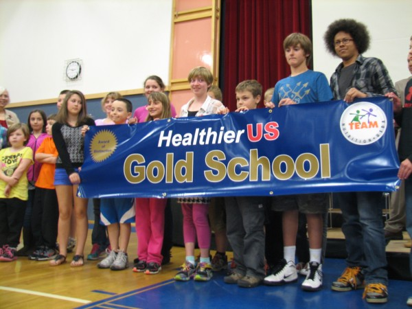 Students at Mount Desert Elementary School hold up a banner Friday in the school gymnasium during an assembly. The school, which has implemented a comprehensive healthful food program was honored Friday as the only one in Maine to receive a Gold of Distinction award from the USDA's HealthierUS School Challenge program.
