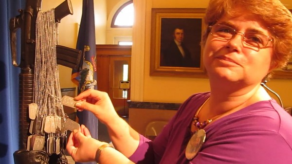 Cindy Small of Wiscasset displays some military dog tags that hang on the Maine Battlefield Cross Memorial at the State House on Friday, May 24, 2013. Army Private Andrew R. Small died in Afghanistan on August 11, 2006.