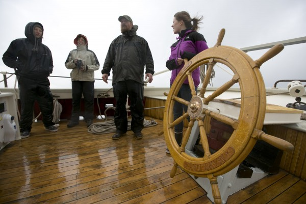 Capt. Barry King schooner Mary Day talks with his deckhands while sailing in the rain off Camden, Maine.
