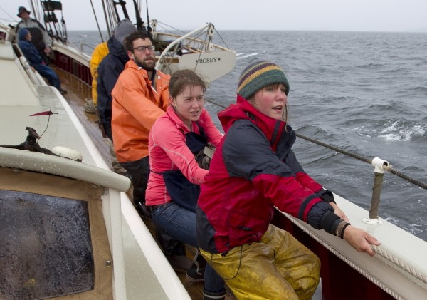 Veteran deckhand Jenny Baxter (right), 24, and mess mate Phoebe Walsh, 18, lead group hoisting a sail on the schooner Mary Day, off the coast of Camden, Maine.