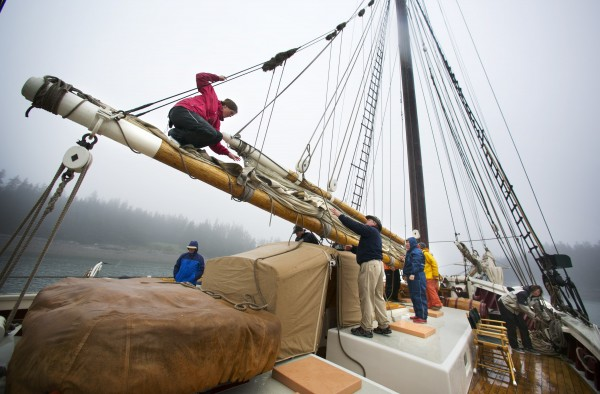 First mate Rebecca Johnson stands on a spar to lead a group taking down the foresail on the Mary Day.